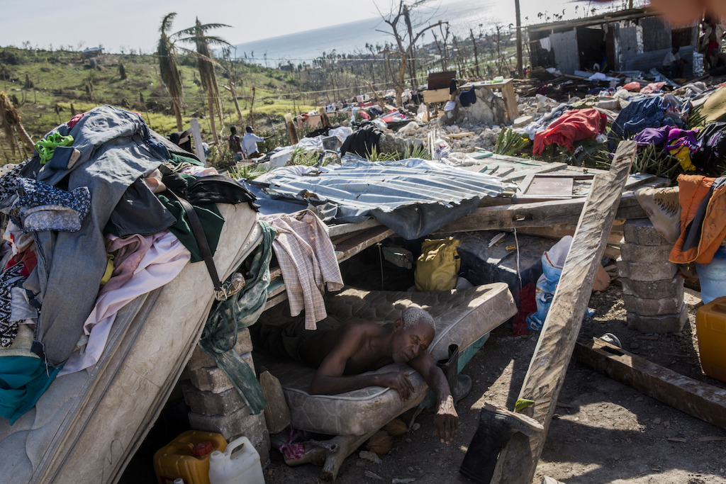 A man who is too ill to walk rests in a makeshift shelter on the site of his destroyed home, in Roche-a-Bateau suffered widespread destruction with many homes destroyed, in southwestern Haiti. Hurricane Matthew through the Caribbean on October 4 and devastated large parts of the island. Photographer: Andrew McConnell/Panos Pictures