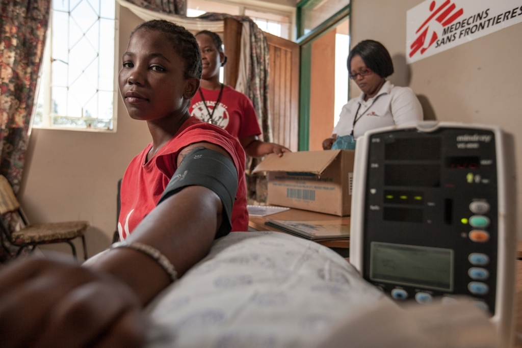 Twenty-six-year-old Londiwe, a young mother, gets her blood pressure taken by a Medecins Sans Frontieres (MSF) nurse at the Community Adherence Club she's attending at King Dinizulu Clinic in Eshowe, KwaZulu-Natal. She is among 30 stable HIV+ patients who attend the club once every two months to have their health checked and receive their ARVs. This relieves people living with HIV of the hassle of sitting in long queues for 1-on-1 visits, and reduces the strain on an already overburdened public health system. Photographer: Greg Lomas / Médecins Sans Frontières