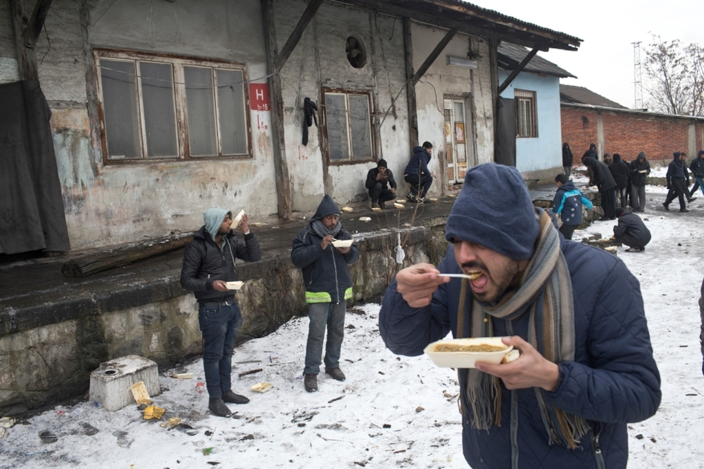 People eat meals outside an abandoned railway warehouse used as shelter by refugees in Belgrade. Photographer: Marko Drobnjakovic