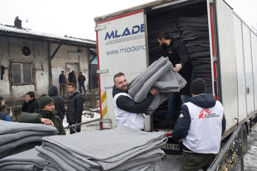 Igor Kuhar, center, and Goran Bakic, right, Medecins Sans Frontieres (MSF) staffers, unload blankets from a truck while distributing aid to refugees in Belgrade, Serbia.  Photographer: Marko Drobnjakovic