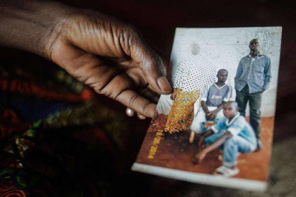 "MSF159645<br/>Alima shows a photograph of her son, Amousa who was 23 years old at the time of his death (right, 1st row)<br/><br/>He was treated at the Red Cross Center after he became ill due to the living conditions in the camp.<br/><br/>Alima is trying to cope by relying on the help of other people living with her in the camp, as she and her husband are unemployed. ""We were born here, our parents and grandparents too... and now we are treated as strangers&quot;."