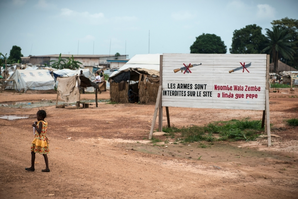 "Girl near ""no weapon"" sign in Mpoko IDP camp at Bangui International Airport. Photographer: Yann Libessart/MSF"