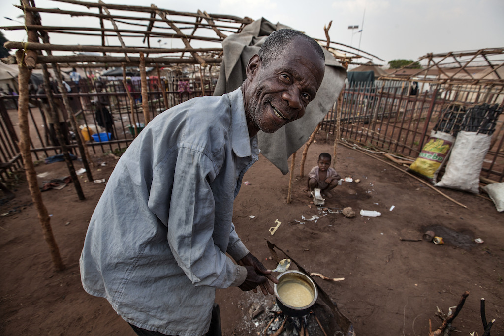 A refugee prepares his meal at the refugee camp in Cacanda. MSF teams also collaborate in establishing the initial provision of water and sanitation in the camp. Photographer: Bruno Fonseca