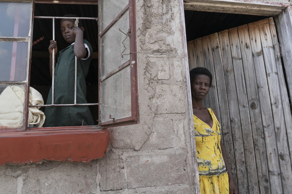 Five year old Shamiso looks through the window of her home after returning from school, alongside her mother, Prisca, at her modest one room home in Epworth on Harare's outskirts. <br/><br/>44 year old Prisca started HIV treatment in 2008. Prisca joined the Epworth HIV program in 2011. Her daughter, Shamiso was born in January 2011, while her mother was part of the Prevention of Mother to Child Transmission program (PMTC). As a result, Shamison was born HIV negative. Photographer: Rachel Corner/De Beeldunie