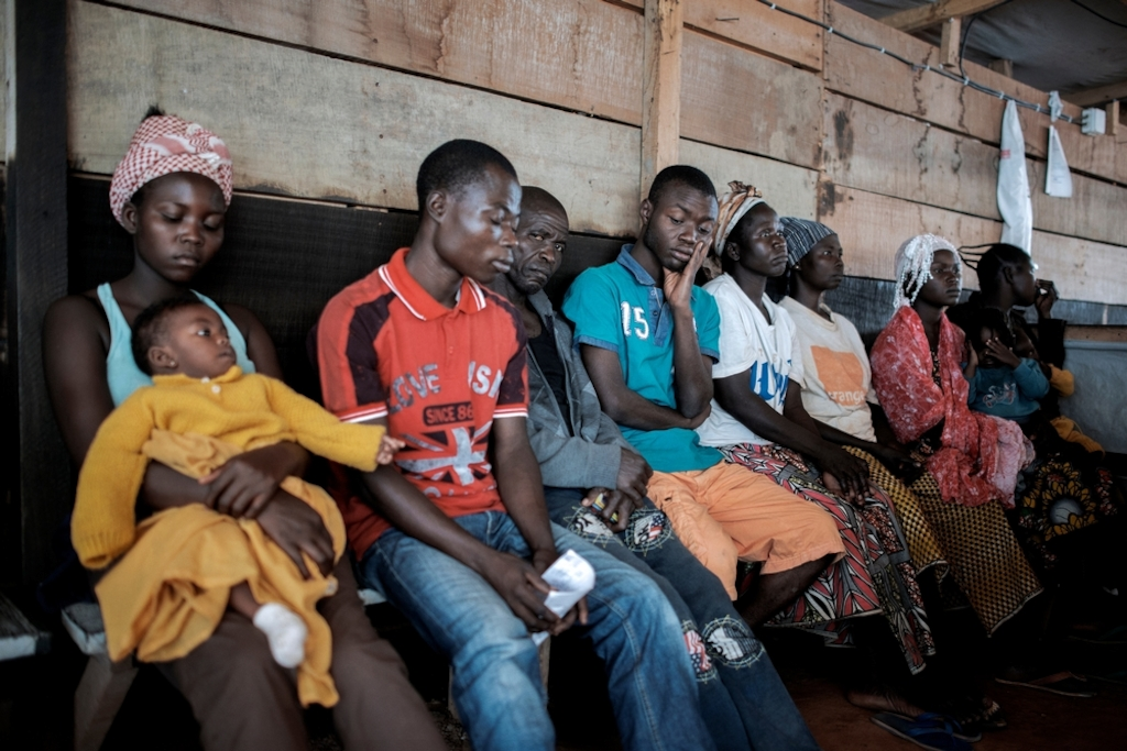 People wait to be seen at a Medecins Sans Frontiers (MSF) hospital at a displaced person camp in M'Poko, Bangui. Photographer: Luca Sola