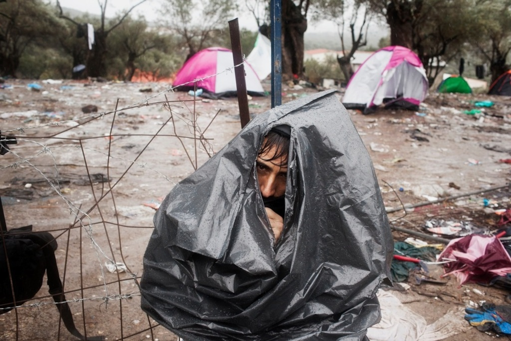 Photographer: Alessandro Penso<br/><br/>Caption: An Afghan refugee wears a rubbish bag to keep himself dry during a rainstorm at the Moria Reception Centre while he waits for his documents on the island of Lesbos.
