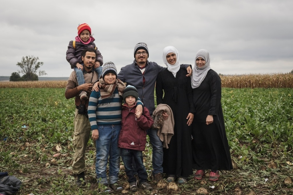 Photographer: Achilleas Zavallis<br/><br/>Caption: Portrait of an extended family from Idleb, Syria (left to right)<br/>Leen (4) sits on the shoulders of her uncle Obaida (31), Abdullah (14), Wallied (5), Mohammed (29), Bayan (18), Suha (32), while they wait on the Serbian side of the Sid - Tovarnik border crossing to enter Croatia.
