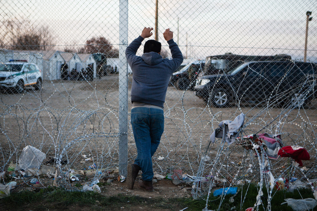 A man looks through the border fence into Macedonia (FYROM). Photographer: Alex Yallop