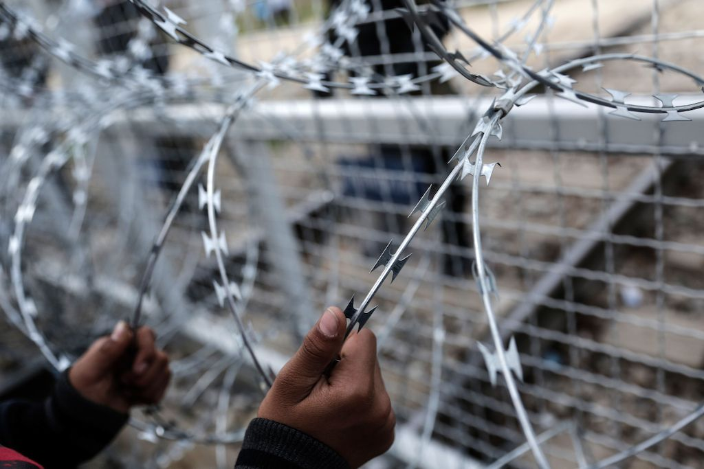 Konstantinos Tsakalidis/SOOC. An Afghan child holds the fence during protest at the Greek-Macedonian (FYROM) border near the northern Greek village of Idomeni.