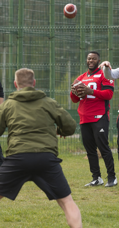 Charleston Hughes leading a football drill with military members deployed on OP UNIFIER in Starychi, Ukraine. Photo: MCpl Mathieu Gaudreault, Canadian Forces Combat Camera