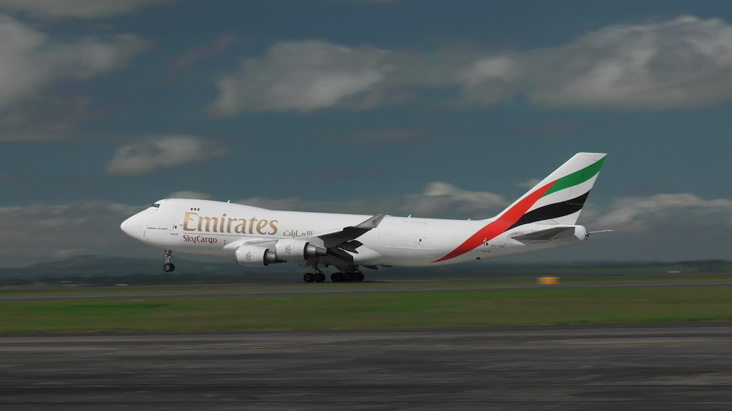 Emirates SkyCargo freighter taking off from Auckland with Emirates Team New Zealand's boat