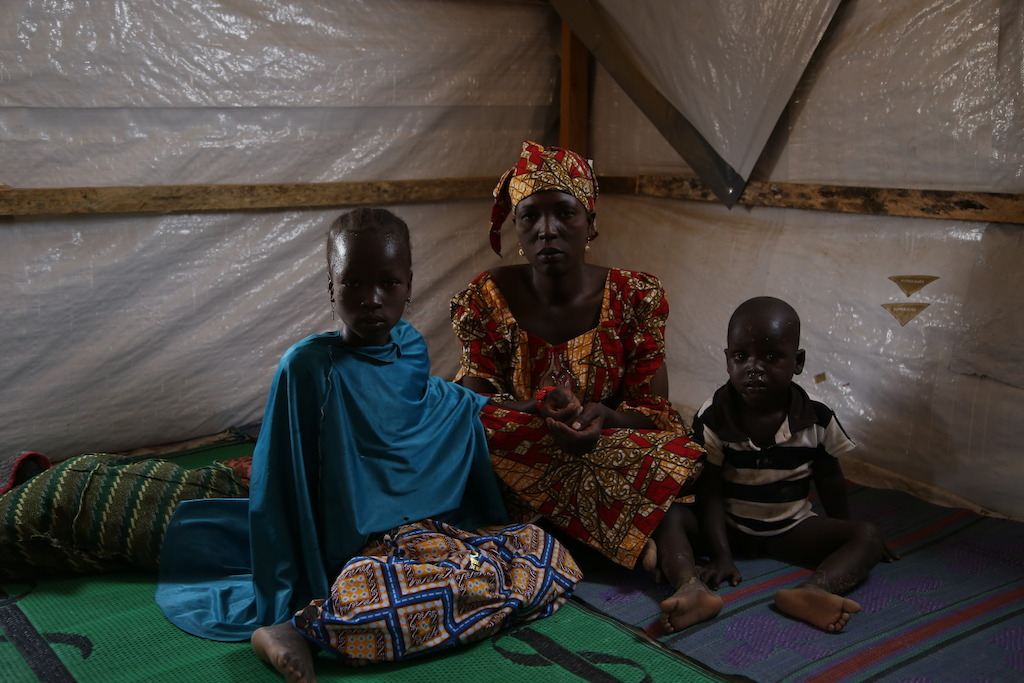A mother with her two children at a camp for internally displaced people in the northeastern Nigerian town of Pulka. Photographer: Igor Barbero