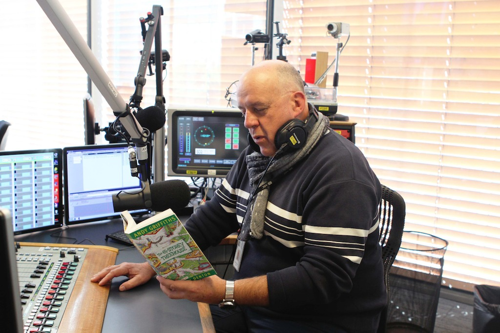 Mornings Presenter, Steve Austin, with his daughter's favourite book, 65-storey Treehouse