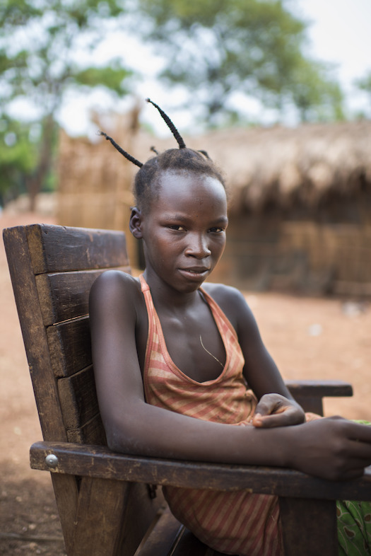 "Credit Colin Delfosse. Solange, 12, Aviation IDP camp, Bambari. She was living with her grandparents when her village was attacked . ""They killed whole families, so together with twenty other villagers we fled to hide in the bush. We slept on mats made of leaves and ate what we could find"". She reunited with her mother at Aviation IDP camp. Solange would like to be a nurse when she grows up."