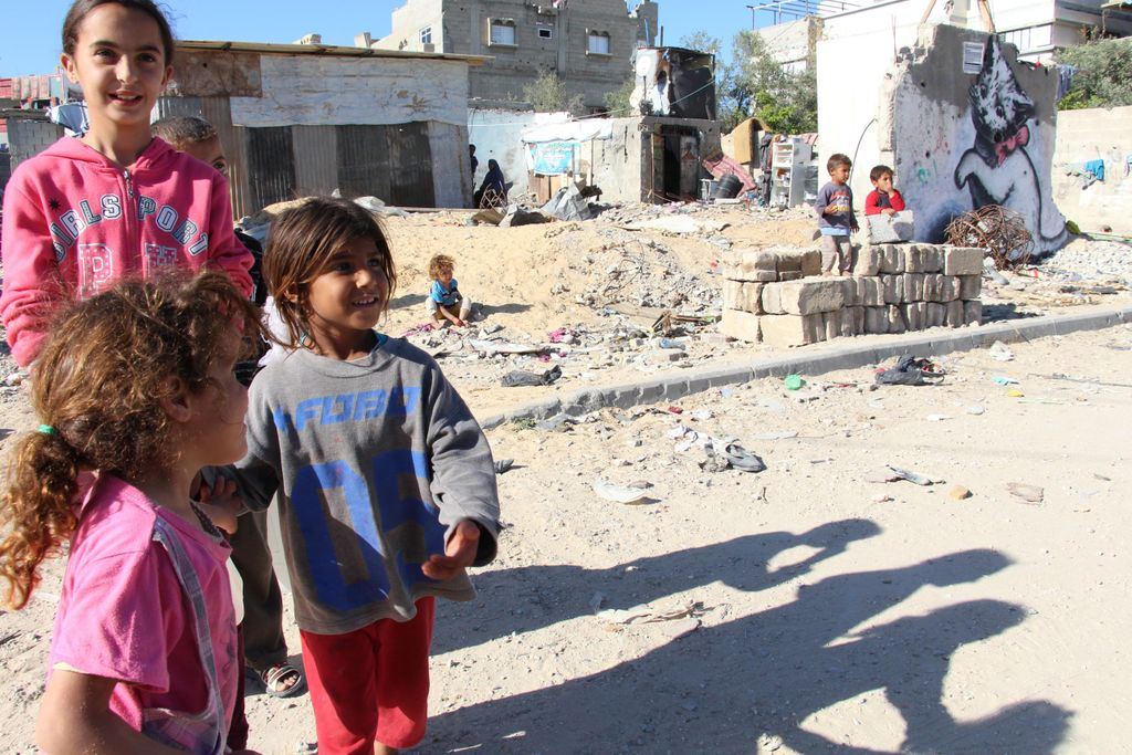 Beit Hanoun in north Gaza strip, severely hit by last war, still many destroyed houses - children of the neighbourhood in front of Banksy mural of the cat, near the UNRWA school which still hosts 53 families who lost their homes during Protective Edge. © Susanne Doettling/MSF