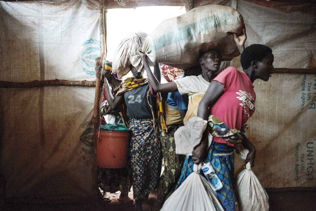 Newly arrived Burundian refugees enter the tent where they will stay in Nyarugusu. During the last weeks, the camp has received hundreds of new refugees every day. Photographer: Luca Sola
