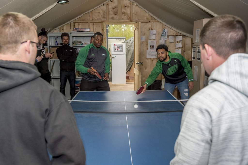 Henoc Muamba (L) and Nic Demski (R) playing ping pong with military members deployed on OP UNIFIER in Starychi, Ukraine. Photo: MCpl Mathieu Gaudreault, Canadian Forces Combat Camera